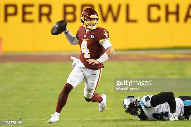 Taylor Heinicke of the Washington Football Team scrambles with the ball away from the tackle of Efe Obada of the Carolina Panthers during the third...