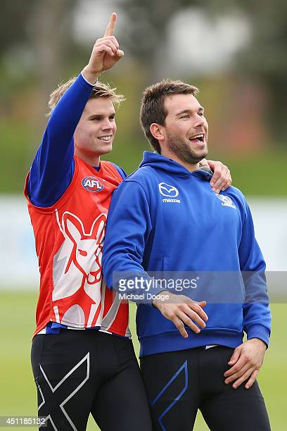 Taylor Hine and Levi Greenwood celebrate a goal during a North Melbourne Kangaroos AFL training session at Arden Street Ground on June 25 2014 in...