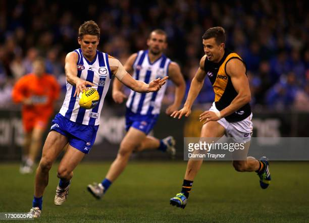 Taylor Hine of the Kangaroos kicks the ball as Brett Deledio of the Tigers gives chase during the round 15 AFL match between the North Melbourne...