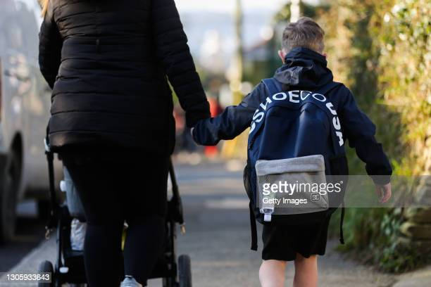 Taylor Hoare walks to school with mother Brie Hoare, with hand sanitiser attached to his bag on March 08, 2021 in Truro, England. England's schools...