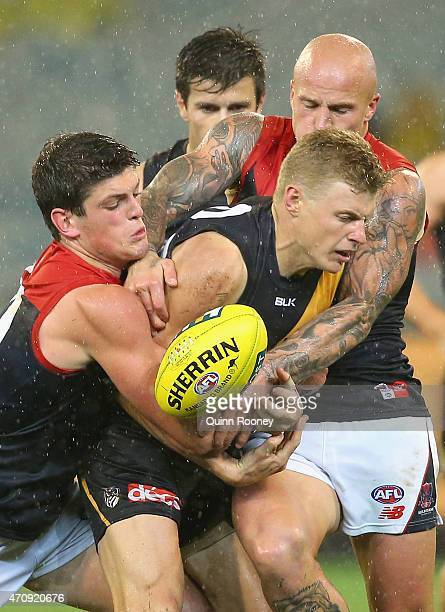 Taylor Hunt of the Tigers is tackled by Angus Brayshaw and Nathan Jones of the Demons during the round four AFL match between the Richmond Tigers and...