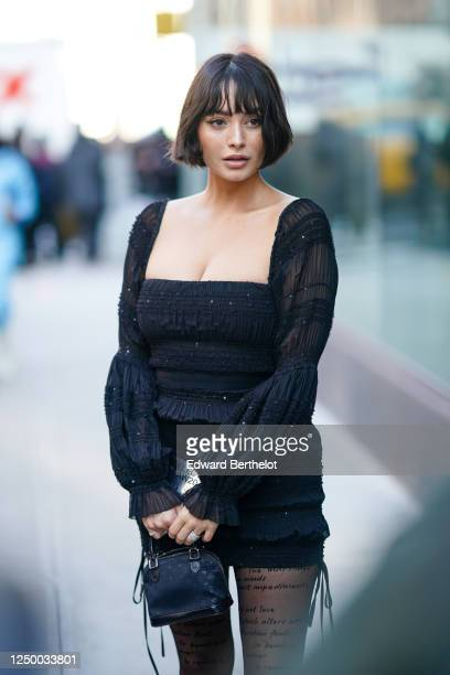 Taylor LaShae wears a black lace mesh ruffled dress with embroidery, a navy blue long wool vest, a Vuitton bag, tights with printed words, outside...