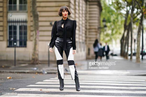 Taylor Lashae wears a black long sleeves top with a lavaliere, a black lace bra, a black leather crop pants with white leather inserts, embossed...