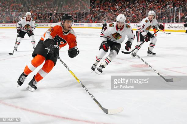 Taylor Leier of the Philadelphia Flyers skates against Nick Schmaltz and Connor Murphy of the Chicago Blackhawks on November 9 2017 at the Wells...