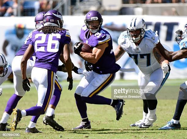 Taylor Lewan of the Tennessee Titans lines up to tackle Andrew Sendejo of the Minnesota Vikings as he carries the ball after recovering a fumble...