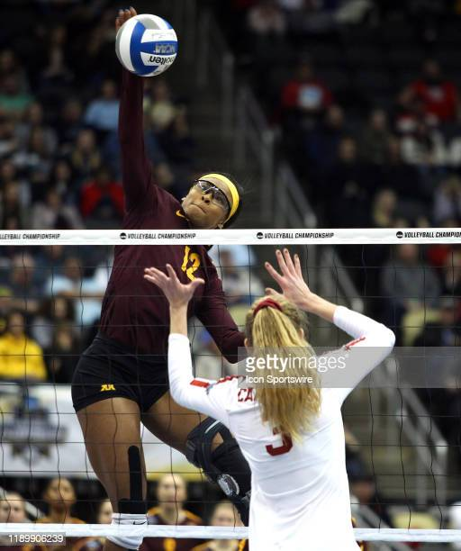 Taylor Morgan of the Minnesota Golden Gophers spikes the ball as holly Campbell of the Stanford Cardinal attempts a block during the NCAA Division 1...
