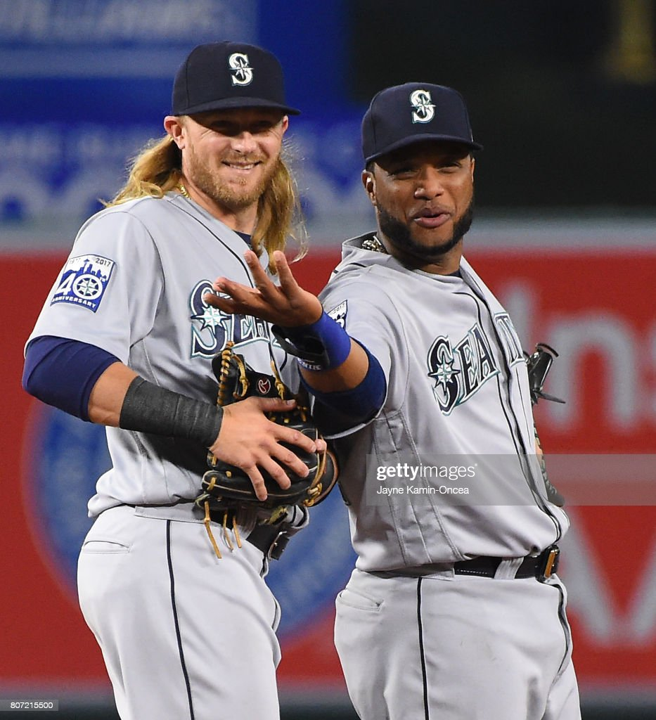 Taylor Motter #21 of the Seattle Mariners and Robinson Cano #22 of the Seattle Mariners laugh as they look into the dugout after the last out of the game against the Los Angeles Angels of Anaheim at Angel Stadium on June 30, 2017 in Anaheim, California. Mariners won 10-0.