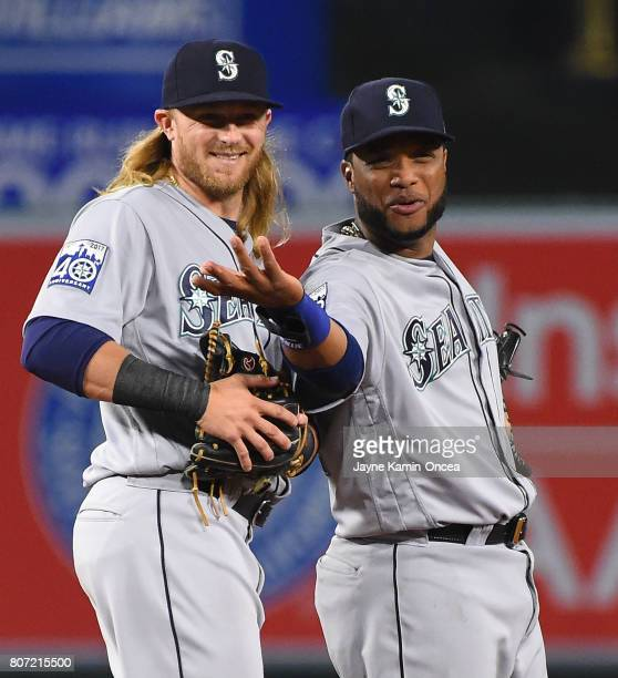 Taylor Motter of the Seattle Mariners and Robinson Cano of the Seattle Mariners laugh as they look into the dugout after the last out of the game...