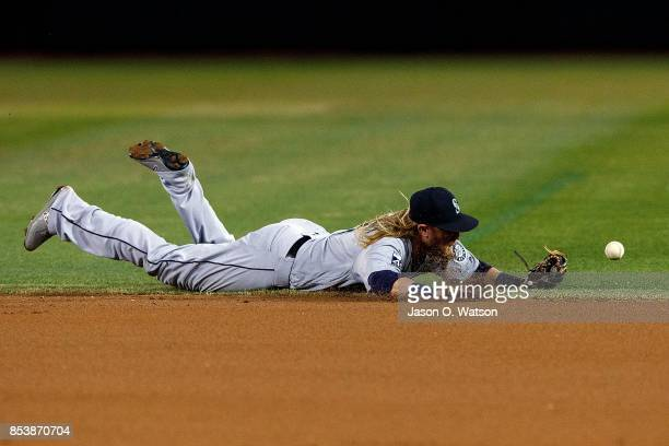 Taylor Motter of the Seattle Mariners dives for but is unable to field a ground ball hit off the bat of Matt Joyce of the Oakland Athletics during...