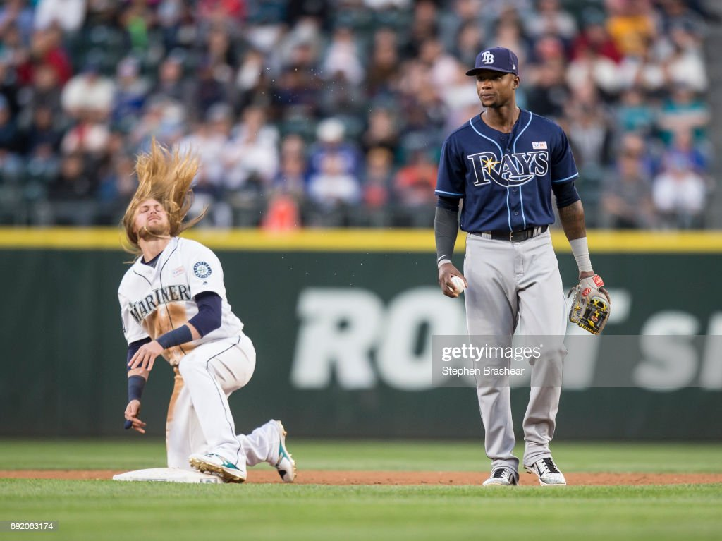 Taylor Motter #21 of the Seattle Mariners flips his hair after stealing second base, beating the tag of shortstop Tim Beckham #1 of the Tampa Bay Rays during the fourth inning of a game at Safeco Field on June 3, 2017 in Seattle, Washington.
