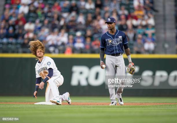 Taylor Motter of the Seattle Mariners flips his hair after stealing second base beating the tag of shortstop Tim Beckham of the Tampa Bay Rays during...