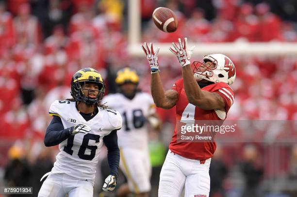 J Taylor of the Wisconsin Badgers catches a pass in front of Jaylen KellyPowell of the Michigan Wolverines during the third quarter of a game at Camp...