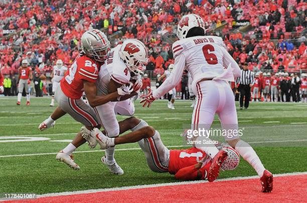 Taylor of the Wisconsin Badgers falls into the end zone for a touchdown in the third quarter while being tackled by Shaun Wade and Jeff Okudah of the...