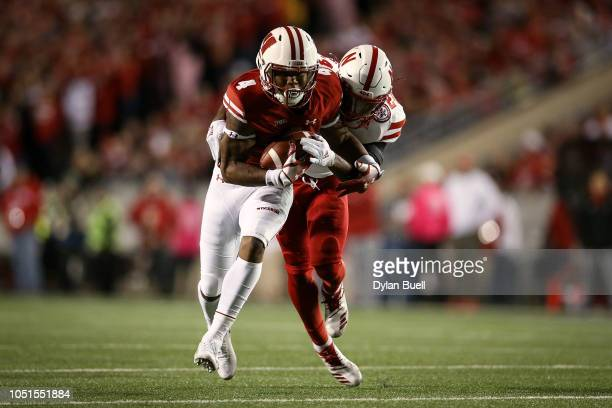 J Taylor of the Wisconsin Badgers runs with the ball while being tackled by Aaron Williams of the Nebraska Cornhuskers in the second quarter at Camp...