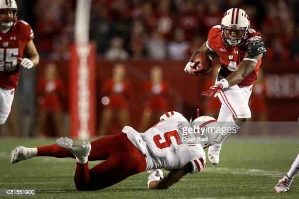 J Taylor of the Wisconsin Badgers runs with the ball while being tackled by Dedrick Young II of the Nebraska Cornhuskers in the second quarter at...
