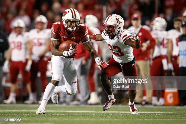 J Taylor of the Wisconsin Badgers runs with the ball while being chased by Dicaprio Bootle of the Nebraska Cornhuskers in the third quarter at Camp...