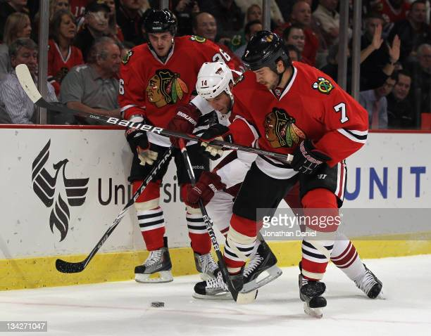 Taylor Pyatt of the Phoenix Coyotes battles for the puck between Dave Bolland and Brent Seabrook of the Chicago Blackhawks at the United Center on...