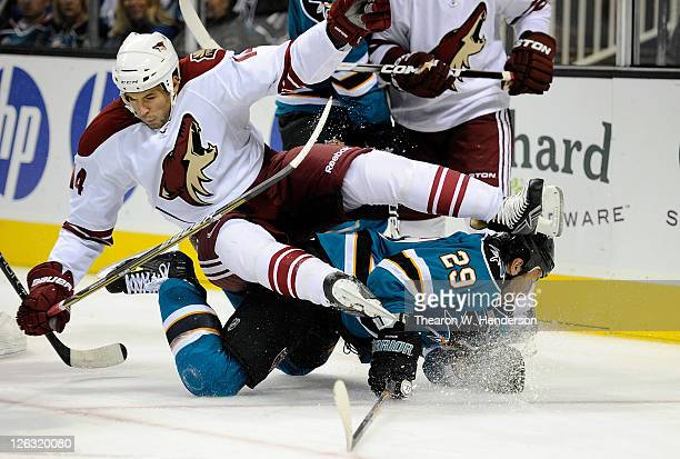 Taylor Pyatt of the Phoenix Coyotes is knocked off his skates by Ryane Clowe of the San Jose Sharks in the third period during an NHL preseason...