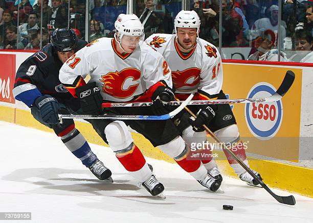 Taylor Pyatt of the Vancouver Canucks reaches around to check David Hale of the Calgary Flames as he skates beside teammate Jeff Friesen during their...