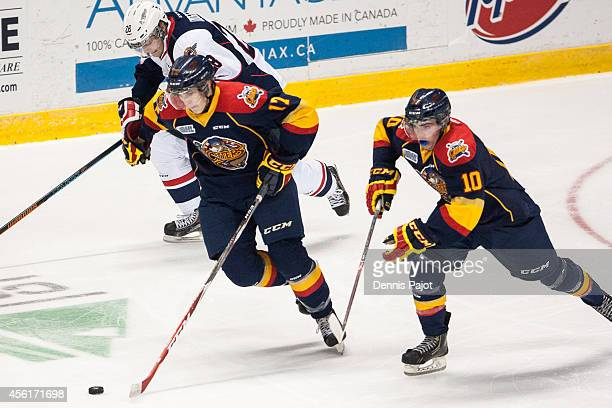 Taylor Raddysh and Shaun Bily of the Erie Otters move the puck against Slater Doggett of the Windsor Spitfires on September 26 2014 at the WFCU...