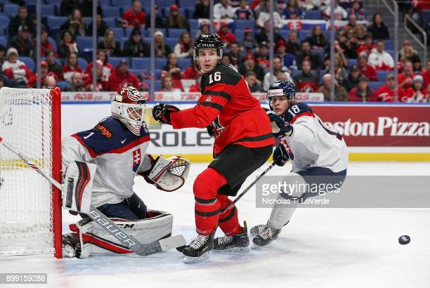 Taylor Raddysh of Canada tracks a rebound off the pad of goaltender Dávid Hrenák of Slovakia with Adam Liska of Slovakia entering the play during the...