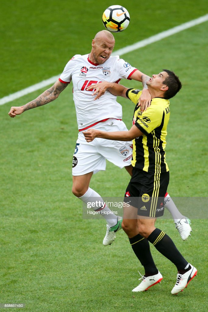 Taylor Regan of Adelaide United wins a header over Andrija Kaludjerovic of the Phoenix during the round one A-League match between Wellington Phoenix and Adelaide United at Westpac Stadium on October 8, 2017 in Wellington, New Zealand.