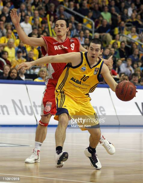 Taylor Rochestie of Berlin challenges for the ball with Karsten Tadda of Bamberg during the Beko Basketball Bundesliga match between Alba Berlin and...