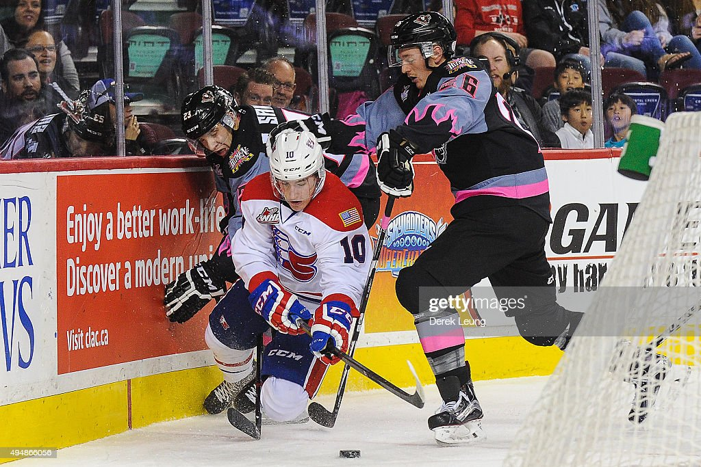 Taylor Sanheim #23 (L) and Connor Rankin #26 of the Calgary Hitmen check Ethan McIndoe #10 of the Spokane Chiefs during a WHL game at Scotiabank Saddledome on October 29, 2015 in Calgary, Alberta, Canada.