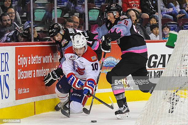 Taylor Sanheim and Connor Rankin of the Calgary Hitmen check Ethan McIndoe of the Spokane Chiefs during a WHL game at Scotiabank Saddledome on...