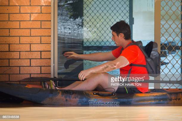 Taylor Shergold tries to open the front door of his mother's home which was partially submerged by floodwaters caused by Cyclone Debbie in North...