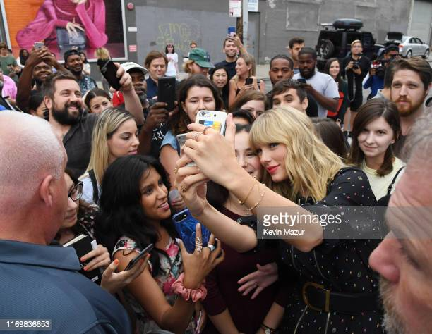 Taylor Swift poses with fans at the Spotify Mural on Album Release Day at Kent Avenue and South 1st Street Williamsburg on August 23 2019 in Brooklyn...