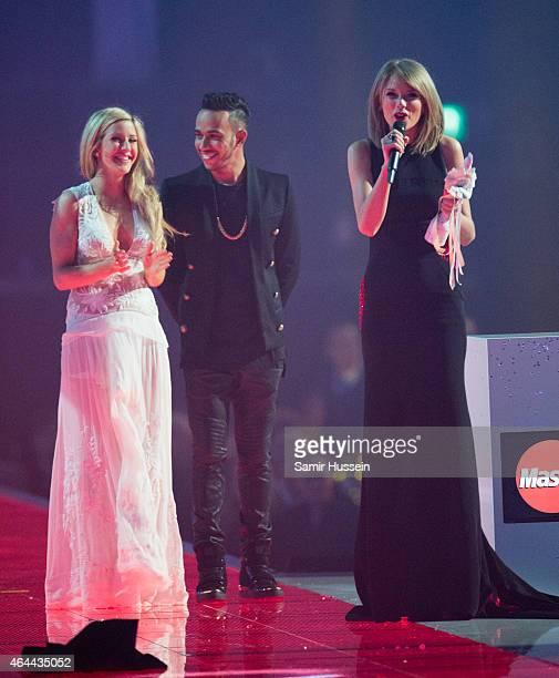 Taylor Swift wins the International female solo artist award as Ellie Goulding and Lewis Hamilton look on at the BRIT Awards 2015 at The O2 Arena on...