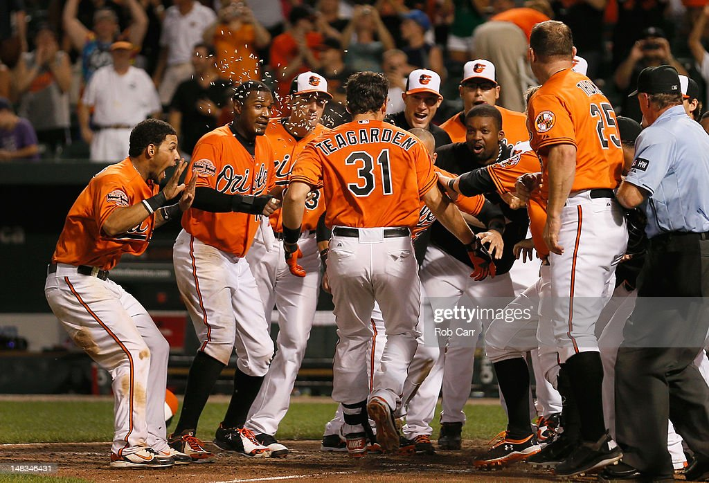 Taylor Teagarden #31 of the Baltimore Orioles is mobbed by teammates after hitting the game winning home run to defeat the Detroit Tigers 8-6 in thirteen innings at Oriole Park at Camden Yards on July 14, 2012 in Baltimore, Maryland.