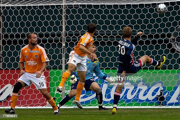 Taylor Twellman of the New England Revolution scores the first goal of the game past goalie Pat Onstad of the Houston Dynamo as Eddie Robinson and...