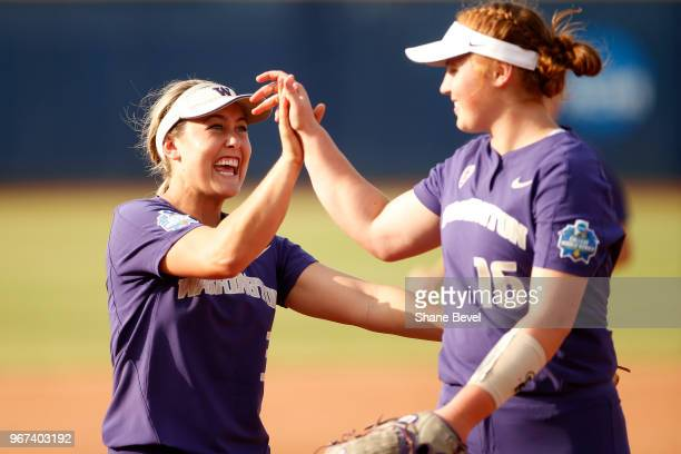 Taylor Van Zee and Gabbie Plain of the Washington Huskies high five during the Division I Women's Softball Championship held at USA Softball Hall of...
