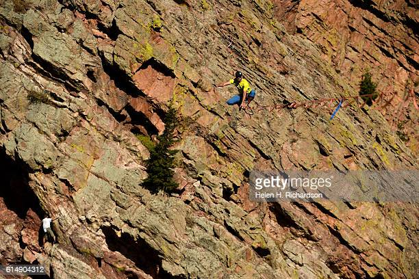 Taylor VanAllen high above a rock climber to the left makes the FA or First Across on a highline from the Wind Tower rock formation to the Bastille...