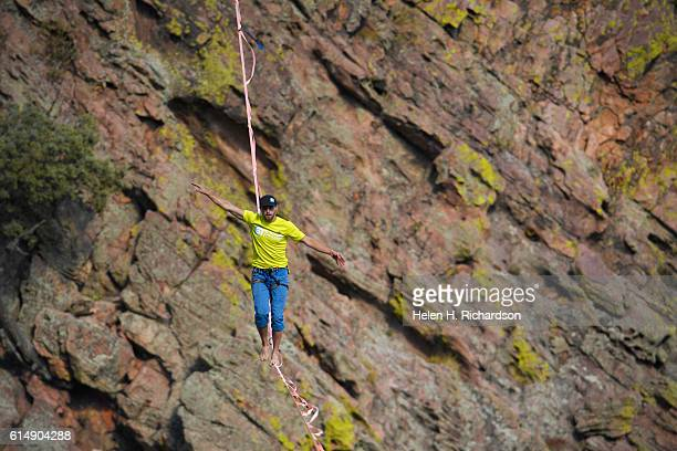 Taylor VanAllen makes the FA or First Across on a highline from the Wind Tower rock formation to the Bastille rock formation 450 feet off the ground...