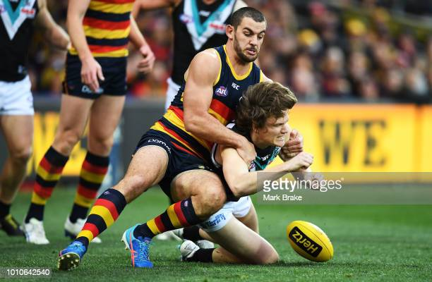 Taylor Walker of the Adelaide Crows tackles Jared Polec of Port Adelaide during the round 20 AFL match between the Adelaide Crows and the Port...