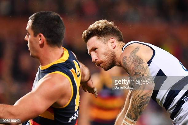 Taylor Walker of the Crows bumps Zach Tuohy of the Cats during the round 17 AFL match between the Adelaide Crows and the Geelong Cats at Adelaide...
