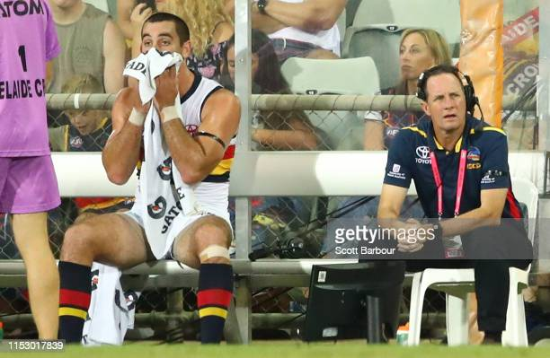 Taylor Walker of the Crows sits on the bench next to Don Pyke ,coach of the Crows during the round 11 AFL match between the Melbourne Demons and the...