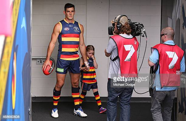 Taylor Walker of the Crows takes hold of the crying mascot when walking out during the round one AFL match between the Adelaide Crows and the North...