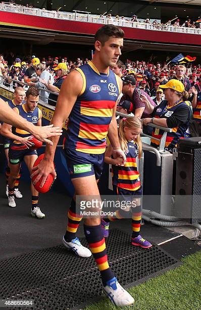 Taylor Walker of the Crows walks out with a crying mascot during the round one AFL match between the Adelaide Crows and the North Melbourne Kangaroos...