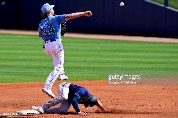 Taylor Walls of the Tampa Bay Rays turns a double play as Jake Cave of the Minnesota Twins slides into second base during the third inning during a...