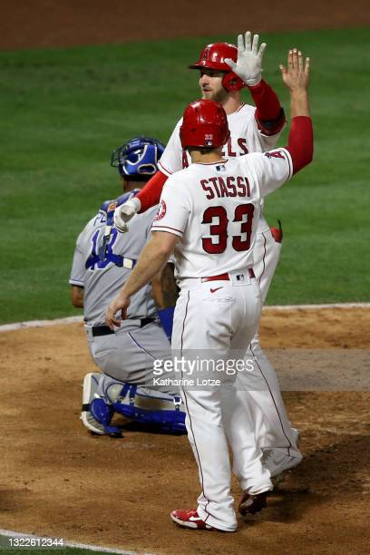 Taylor Ward of the Los Angeles Angels high-fives Max Stassi after hitting a home run in eighth inning against the Kansas City Royals at Angel Stadium...
