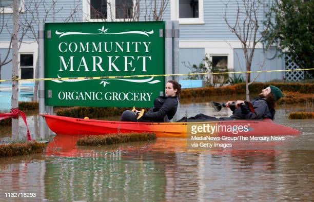 Taylor Weber left and Nicco Weisskoff paddle through flood waters from the Laguna de Santa Rosa near The Barlow market in Sebastopol Calif on...