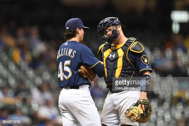 Taylor Williams of the Milwaukee Brewers speaks with Stephen Vogt during the ninth inning of a game against the Cincinnati Reds at Miller Park on...