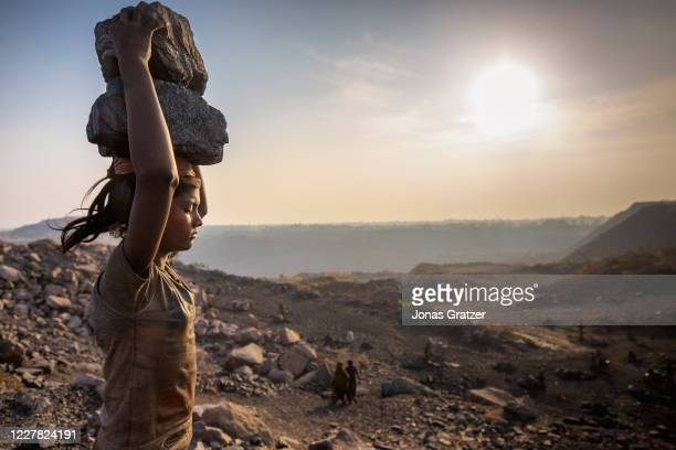 Taymana Kumari, has piled coal on her head while she is working in Jharia coal field where a large amount of indias coal is mined. According to the...