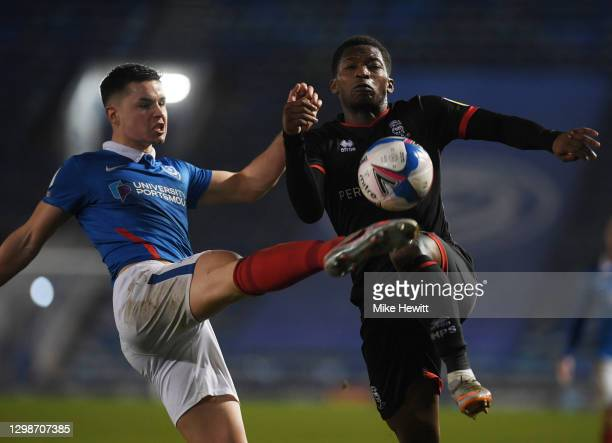Tayo Edun of Lincoln City is challenged by Callum Johnson of PortsmouthFC during the Sky Bet League One match between Portsmouth and Lincoln City at...