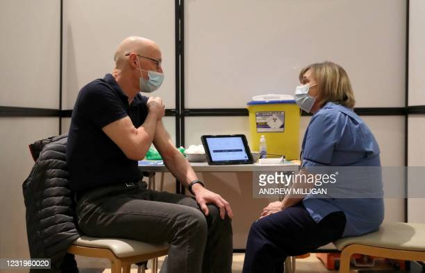 Tayside health worker Beverley Boler chats after administering a dose of Covid-19 vaccine to Scotland's Deputy First Minister John Swinney at...