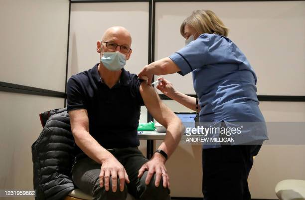 Tayside health worker Beverley Boler prepares to administer a dose of Covid-19 vaccine to Scotland's Deputy First Minister John Swinney at...